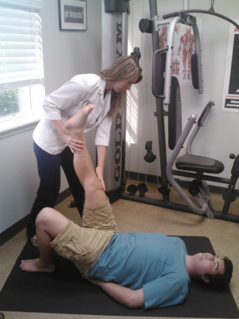Dr. Donnelly with a patient doing leg stretches